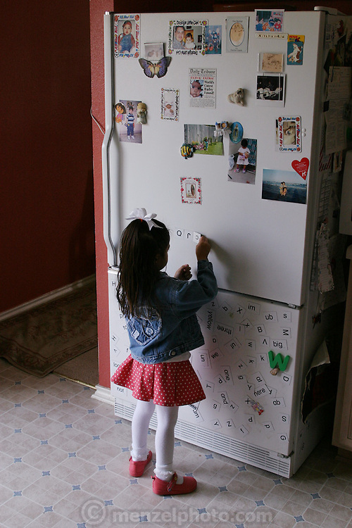 (MODEL RELEASED IMAGE). 4-year-old Brianna Fernandez rearranges the magnets on her family's refrigerator in their home in San Antonia, Texas. (Supporting image from the project Hungry Planet: What the World Eats.)