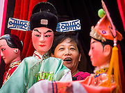 "19 FEBRUARY 2015 - BANGKOK, THAILAND:  A woman sings and manipulates puppets during a Chinese opera for Chinese opera on Yaowarat Road in Bangkok. 2015 is the Year of Goat in the Chinese zodiac. The Goat is the eighth sign in Chinese astrology and ""8"" is considered to be a lucky number. It symbolizes wisdom, fortune and prosperity. Ethnic Chinese make up nearly 15% of the Thai population. Chinese New Year (also called Tet or Lunar New Year) is widely celebrated in Thailand, especially in urban areas that have large Chinese populations.   PHOTO BY JACK KURTZ"