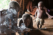 James and Flora smoke home grown tobacco, they start a fire using a bow and drill method.  They are village elders of the traditional Batwa pygmies from the Bwindi Impenetrable Forest in Uganda. They were indigenous forest nomads before they were evicted from the Bwindi Impenetrable Forest when it was made a World Heritage site to protect the mountain gorillas. The Batwa Development Program now supports them.