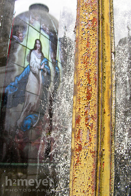 Detail shot of the peeling paint and cobwebs on a mausoleum door framing a stained glass window depicting the Virgin Mary.  Taken at the famous Cementerio de la Recoleta in Buenos Aires, Argentina