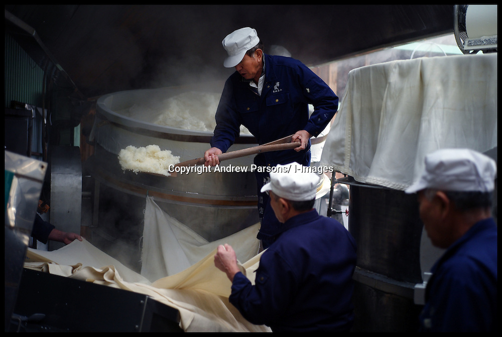 The Japanese Drink Sake being made in a Sake Brewery in Japan. Workers queue up to move the steamed sake rice as a sake brewer unloads the rice from the steamer machine, onto cloth's so it can be taken to the drying rooms quickly as part of the process of making sake at the Urakasumi Sake Brewery in Shiogama, Miyagi, a brewer which was hit by the tsunami in March 2011, Photo By Andrew Parsons/ i-Images