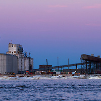 Canada, Manitoba, Churchill, Full moon rises above grain elevators and terminal along Hudson Bay at the Port of Churchill on summer evening.