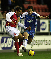 Photo: Paul Thomas.<br />Wigan Athletic v Arsenal. The Barclays Premiership. 13/12/2006.<br /><br />Theo Walcott (L) of Arsenal tries to get away from Leighton Baines.
