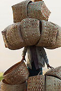 Woman carries big load of weaved baskets on her head to market