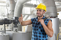 Handsome manual worker gesturing thumbs up in industry