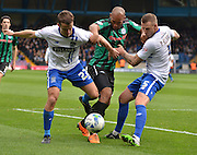 Rochdale Forward, Calvin Andrew is tackled by both Bury defender Danny Pugh and Bury Defender Peter Clarke during the Sky Bet League 1 match between Bury and Rochdale at Gigg Lane, Bury, England on 17 October 2015. Photo by Mark Pollitt.