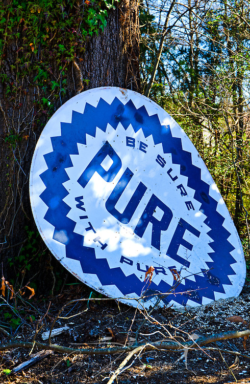 "A Pure Oil sign rests against a tree outside Abe's Grill in Corinth, Miss. on Feb. 26, 2012. Pure was founded in 1914 and still operates in 10 Southern states. The ""Be Sure with Pure"" signs can be found across the South. (Photo by Carmen K. Sisson/Cloudybright)"
