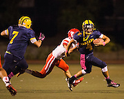 Milpitas quarterback John Keller (4) tries to escape the Saratoga defense during the Homecoming game at Milpitas High School in Milpitas, California, on October 10, 2014. Milpitas beat Saratoga 49-0. (Stan Olszewski/SOSKIphoto)