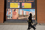Local passer-by and a property development ad on wall in east London borough of Stratford, Newham, home of 2012 Olympics