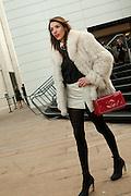 A woman carryi8ng a bright red Chanel handbag outside the pavillion.
