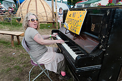 © Licensed to London News Pictures. 27/06/2015. Pilton, UK.  Festival atmosphere at Glastonbury Festival 2015 on Saturday Day 4 of the festival  - a woman festival goer plays a piano.    This years headline acts include Kanye West, The Who and Florence and the Machine, the latter being upgraded in the bill to replace original headline act Foo Fighters. Photo credit: Richard Isaac/LNP