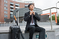 Mid adult businessman with luggage adjusting necktie against buildings