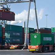 Nederland Zuid-Holland Rotterdam  27-08-2009 20090827 Foto: David Rozing .Serie over logistieke sector.ECT Delta terminal in de haven van Rotterdam. Robotgestuurde wagens vervoeren de containers op de terminal. Een onbemande kraan tilt een container op een wagen. .ECT,European Container Terminals, at the Port of Rotterdam. Europe's biggest and most advanced container terminal operator, handling close to three- quarters of all containers passing through the Port of Rotterdam. ECT is a member of the Hutchison Port Holdings group (HPH), the world biggest container stevedore with terminals on every Continent. At the ECT Delta Terminal unmanned, automated guided vehicles  so called AGVs  transport the containers between ship and stack. In the stack, unmanned automated stacking cranes ( ASCs ) ensure that the containers are always stacked in the correct place. Terminal operations are highly automated for discharging and loading large volumes, wagons, wereldhandel, werk, werkzaamheden, zeehaven, zeehavens..Holland, The Netherlands, dutch, Pays Bas, Europe .Foto: David Rozing