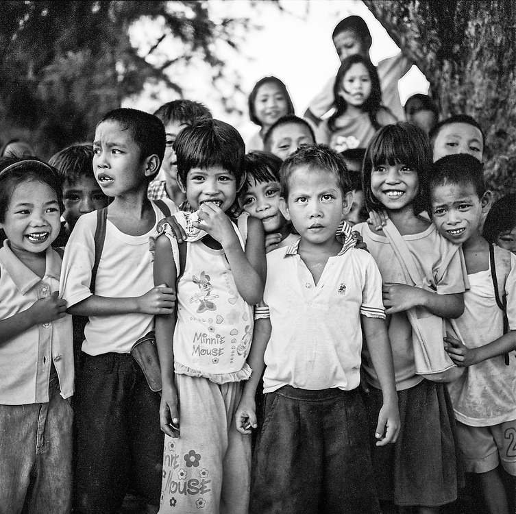A group of children outside their school during recess are intrigued by my camera (an old Rolleiflex) and pose for the shot, Camarines Sur peninsula, Bicol Province, 2008.