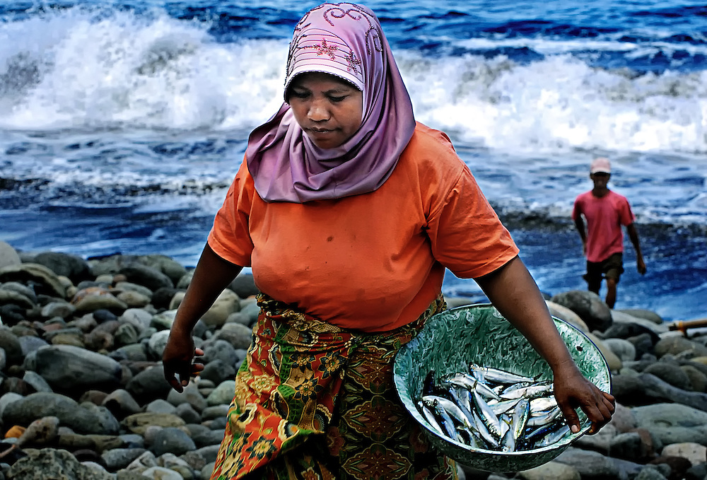 A muslim woman climbs the beach after collecting her husbands fish caught on Lembata Island, Indonesia. Her home and culture is under threat from a open cut mining proposal being supported by the government.
