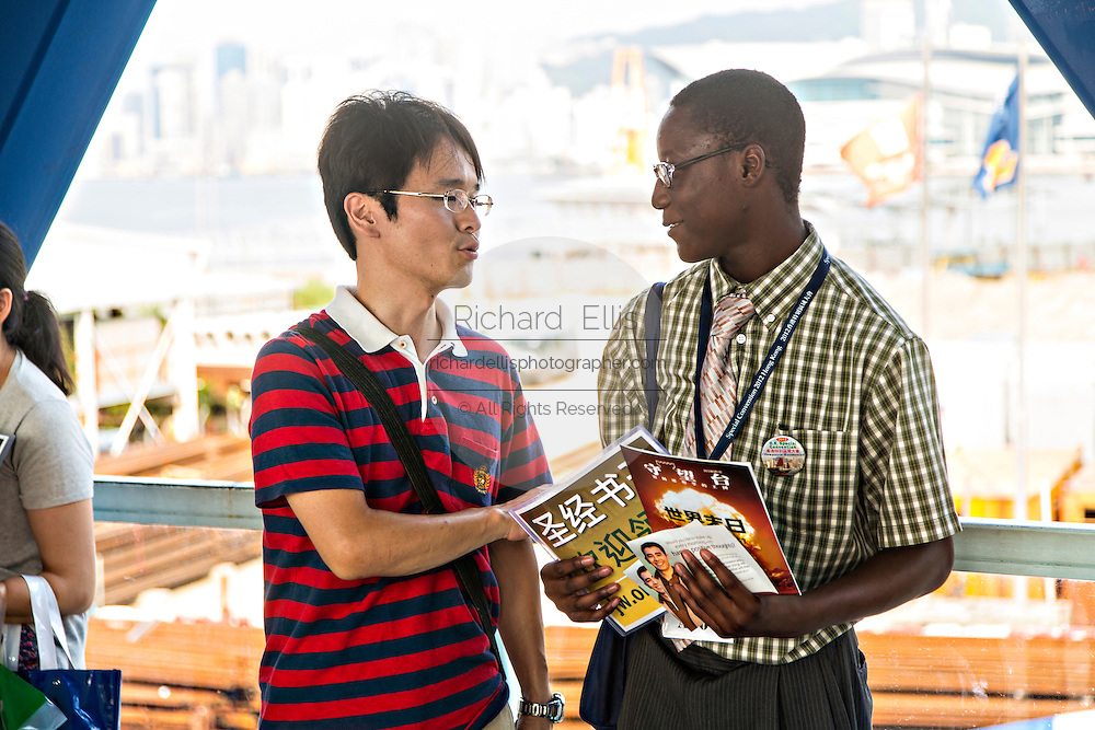 A Christian missionary proselytizes a local resident in Central District Hong Kong.