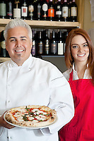 Portrait of a happy chef holding pizza with beautiful waitress