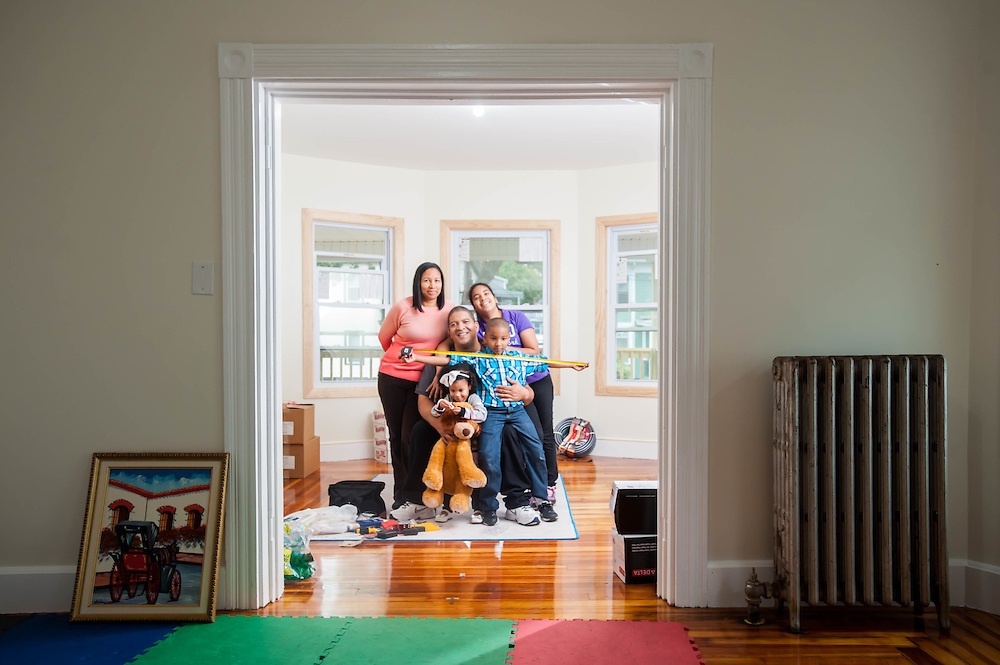 A family stops for a portrait while moving into their new home in Lawrence, MA, photographed for the Mass Housing Annual Report.
