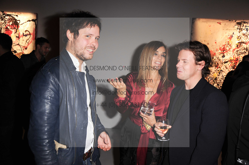 Left to right, Nicolas Pol, Carine Roitfeld and Christopher Kane at a private view of Nicolas Pol's paintings entitled 'Mother of Pouacrus' held at The Dairy, Wakefield Street, London WC1 on 14th October 2010.