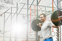Smiling man lifting barbell at crossfit gym