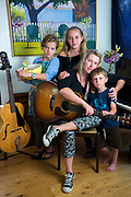 "Musician and Cape Wellness Collaborative founder, Sarah Swain, 44, is photographed in her Harwich home with her three children, from left, Jessie, 10, Lucy, 12 and Stanley, 4. Sarah's mother, grandmother and uncle all passed away from cancer which was the impetus for starting Cape Wellness Collaborative--a non-profit organization that provides integrative wellness therapies for people on the Cape and Islands facing cancer. ""Ironically, I never got around to getting mammograms, I think they subconsciously terrified me due to my family history. After admitting this to my board members, they pretty much forced me to get one,"" she explains. While Sarah's mammogram showed no signs of cancer, she was urged to get genetically tested and discovered she had the CALP2 gene, a rare gene mutation that carries the same risks for cancer as the BRCA2 gene. 'What to do with this information is a very personal decision,"" she explains. ""After losing my mother to cancer when she was 52, it came down to me doing everything in my power to help ensure I am here for my kids,"" she says. Weeks before this photo was taken Sarah underwent a prophylactic double mastectomy and oophorectomy (removal of ovaries and tubes). Around the same time that Sarah found out about her genetic mutation, her husband, Steve, had a heart attack and also discovered he has a genetic heart defect. ""He had to have surgery a few months before me and it was a very intense time for the family,"" she recalls. ""It really makes you aware of what you hold most precious in life,"" she says. Sarah and her husband decided they needed to decompress and reconnect as a family by taking some time away from their lives. ""We took six months and went on a sailing trip down the inter-coastal waterway then through Bahamas and homeschooled the kids,"" she explains. ""It was amazing---the best thing we ever did as a family!"" she adds."
