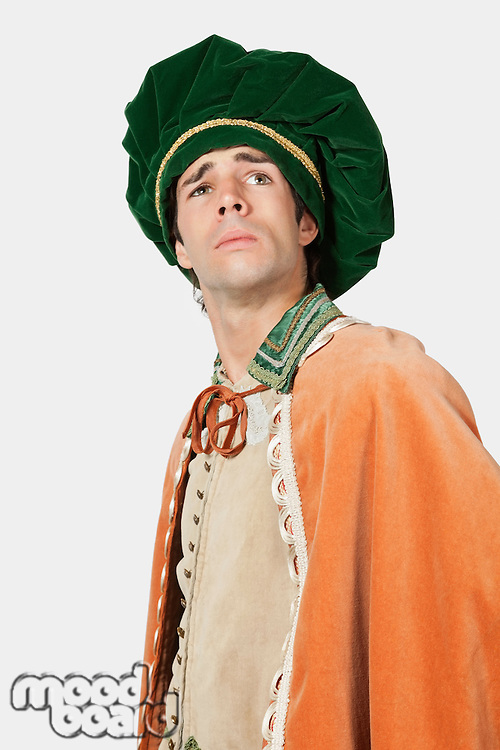 Thoughtful young man in old-fashioned costume looking away against gray background