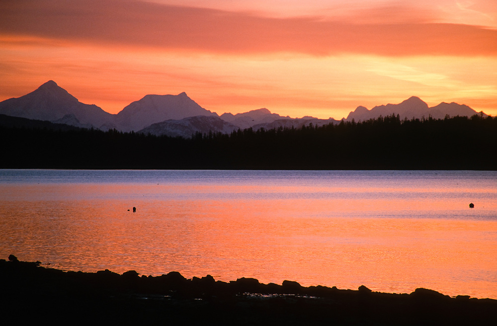 Alaska. Glacier Bay NP. Bartlett Cove. The sun sets behind the Fairweather Range and is reflected in the protected waters of Bartlett Cove.