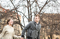 Smiling young man and woman holding hands and walking outdoors