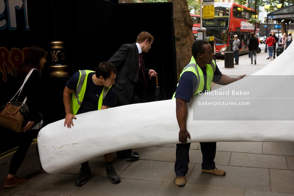 Removals workmen position a prop into a West End theatre while partially blocking pavement to pedestrians on Charing Cross Rd.