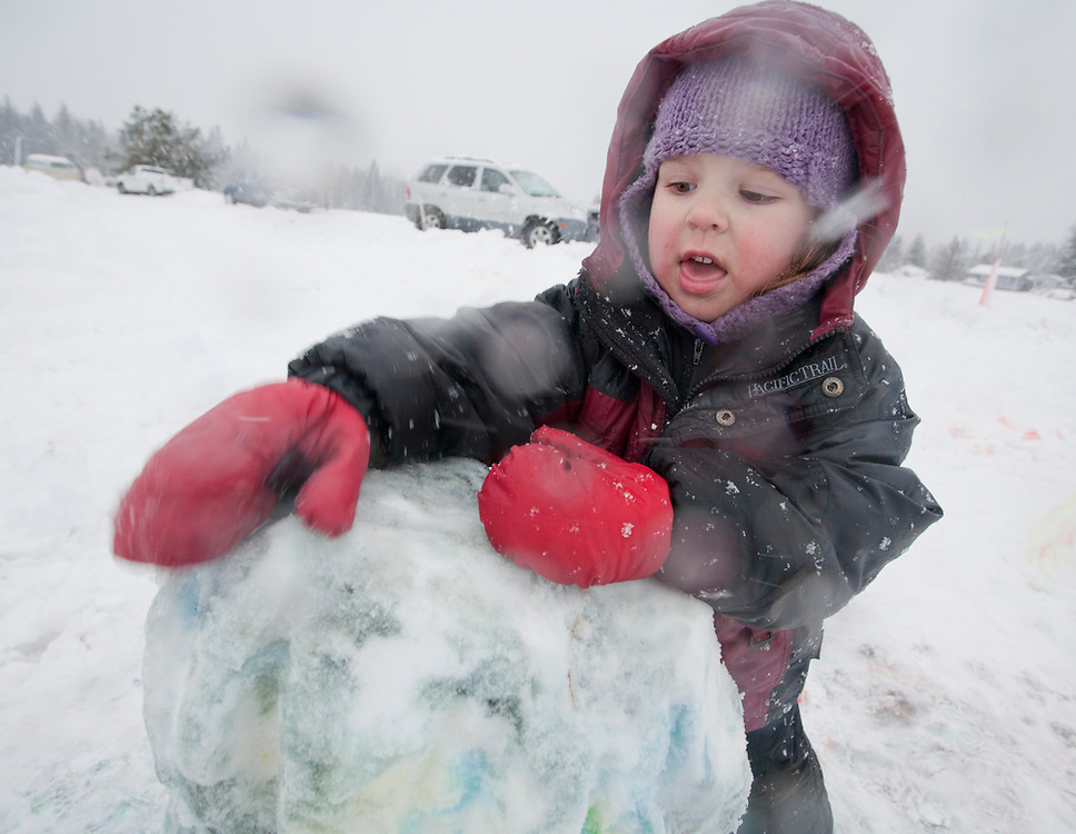 A young child builds a snowman during a heavy snowfall in Gustavus, AK. MR