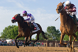 Nyquist with Mario Gutierrez up, left, rounds the final turn and moves on Gun Runner with Florent Geroux up to win the 142nd running of the Kentucky Derby, Saturday, May 07, 2016 at Churchill Downs in Louisville.