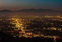 Twilight view of the San Fernando Valley with the San Gabriel Mountains behind, with Van Nuys Boulevard in the middle, shot above Sherman Oaks from Mulholland Drive, Los Angeles, California USA.