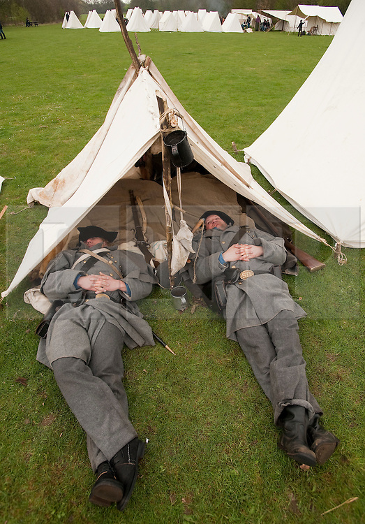 © London News Pictures. 08/04/2012. South Okendon, UK.  Members of the Southern Skirmish Association dressed as Confederate soldiers take a nap at camp before taking part in a reenactment of the final days of the American Cival war at Belhus Wood Country Park near South Okenden, Essex on April 8, 2012. The American Civil war was ended on April 9 (Tomorrow), 1865 when the  Confederate surrendered to the Union. Photo credit :  Ben Cawthra/LNP