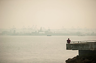 2018 AUGUST 20 - A man fishes in Elliott Bay with the Port of Seattle harbor as a backdrop as smoke fills the skies of Seattle, WA, USA. Seen from near Don Armeni Boat Ramp in West Seattle. By Richard Walker