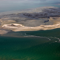Africa, Namibia, Walvis Bay. Aerial view of flamingos in Walvis Bay lagoon, where the Namib Rand desert meets the sea.