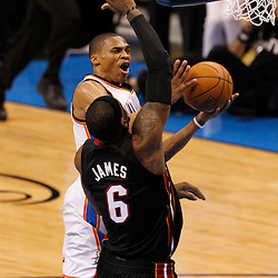 Jun 14, 2012; Oklahoma City, OK, USA;  Oklahoma City Thunder point guard Russell Westbrook (0) drives to the basket against Miami Heat small forward LeBron James (6) during the fourth quarter of game two in the 2012 NBA Finals at Chesapeake Energy Arena. Mandatory Credit: Derick E. Hingle-US PRESSWIRE