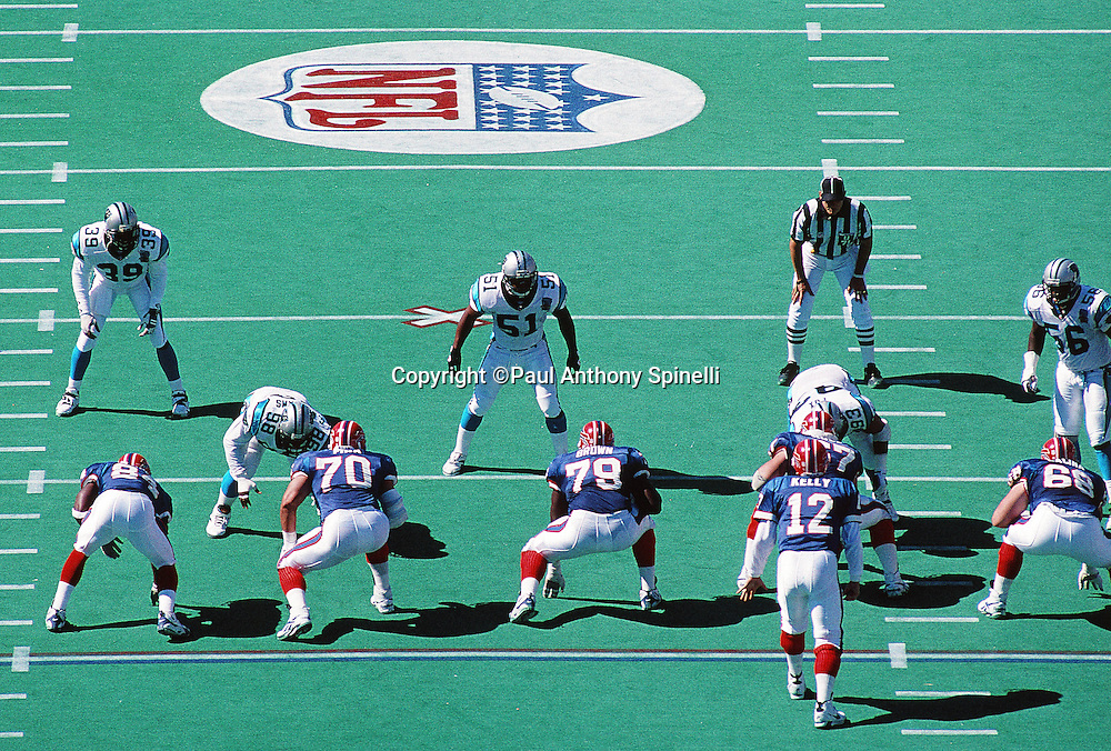 An official looks on as the Carolina Panthers defense gets set while Buffalo Bills quarterback Jim Kelly (12) calls signals in the shotgun formation during the NFL football game against the Buffalo Bills on Sept. 10, 1995 in Orchard Park, N.Y. The Bills won the game 31-9. (©Paul Anthony Spinelli)
