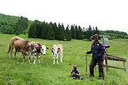 A boy and his mother in a green field with free grazing cows Photographed in Austria