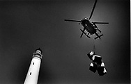 A supply helicopter flies over the lighthouse on the uninhabited island of Hyskeir, eight miles from Rum in the Inner Hebrides on Scotland's west coast. The helicopter was delivering supplies to workmen who were converting the lighthouse from manned to automatic. The lighthouse was operated by the Northern Lighthouse Board and was one of the last in Scotland to be automated.
