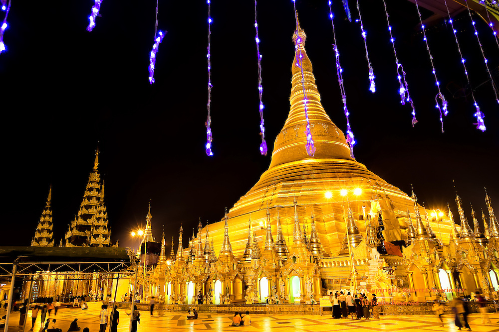 Great Dragon Pagoda: A spectacular night time view of Shwedagon, the golden Great Dragon Pagoda; a festive touch is added to this religious scene with strings of purple lights dangling down from an adjacent temple, Yangon Myanmar.