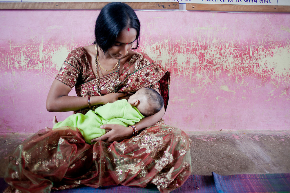 Dolasane. Sangamner Block, Ahmednagar, Maharashtra, India, 23 years old Lalita Kshirsagar breast feeds her one and a half month old son, at the anganwadi center, in Dolsane.   July 2012:.UNICEF India/2012/Vishwanathan.  UNICEF India/2012/Vishwanathan