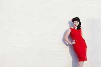 Young beautiful woman in red dress leaning on wall