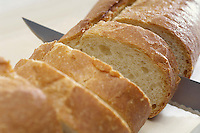 Close-up of knife slicing baguette