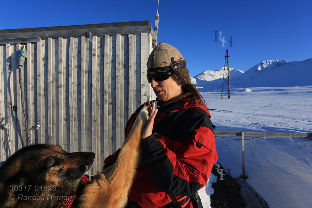Woman high-fives her dog in April snows at the international science village of Ny-Alesund on Spitsbergen island in Kongsfjorden; Svalbard, Norway.