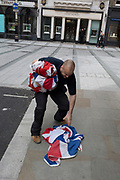 An employee stops to pick up a dropped Union Jack flag from the pavement outside a retailer's Bond Street address, on 5th June 2019, in London, England.