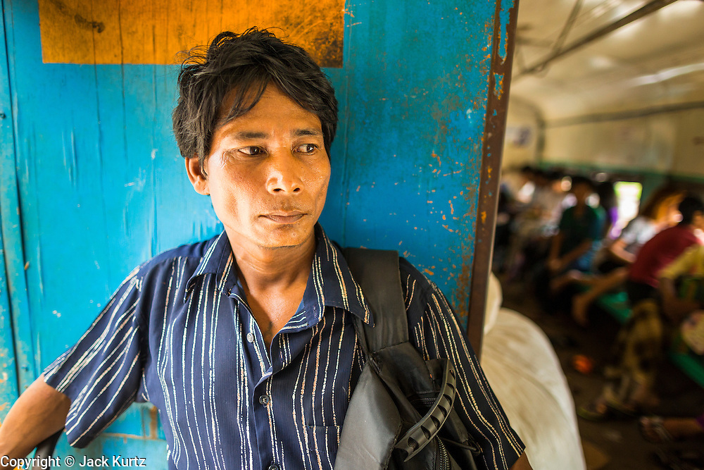 05 JUNE 2014 - YANGON, YANGON REGION, MYANMAR: A man stands in a doorway on the Yangon Circular Train. The Yangon Circular Train is a commuter train that circles Yangon, Myanmar (Rangoon, Burma). The train is 45 kilometers long, makes 38 stops and takes about three hours to make a loop of the city.     PHOTO BY JACK KURTZ