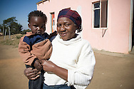 A young boy pictured with his great-grandmother at Mpolongeni child care center, Swaziland. The Kingdom of Swaziland (population 1.1m), a small, landlocked country in southern Africa was bordered by South Africa on three sides and Mozambique to the east, with Mbabane as its administrative capital. At the start of the 21st century, the country had the highest incidence per head of population of HIV/Aids in the world and and high levels of poverty mainly in rural areas where 75 per cent of the population lived.