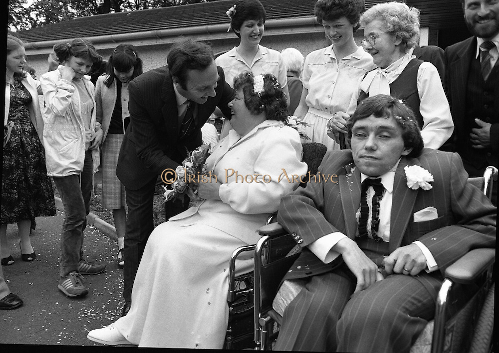 Historic Wedding Bells For Disabled Couple,  (N81)..1981..20.06.1981..06.20.1981..20th June 1981..Happy wedding bells chimed today for the first disabled couple in residential care to marry in the Republic of Ireland. The happy couple are Marie Skully and Pat Linehan and they were married in a special ceremony in The Cara Cheshire Home in the Phoenix Park. Both Marie and Pat are confined to wheelchairs because of their disabilities. After honeymoon, they will make their home in specially adapted quarters within the Cheshire residence..The Minister for Health, Dr Michael Woods,is pictured wishing the couple well for the future.