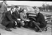 Dunlop Total Mobility Tyre At Mondello Park..1972..13.10.1972.10.13.1972..13th October 1972..A revolutionary new tyre development which can end the hazardous effects of a blowouts and punctures was announced by Dunlop.The T4 Total Mobility Tyre is designed to allow the motorist to continue for a distance of up to 100 miles at speeds of 50mph even if the tyre is deflated. The tyre is designed to enable the driver maintain control of the vehicle in the event of a blowout...Picture taken after the tyre test on the alternate test vehicle,Mr P J McGovern,Chief engineer,Dept Local Government, Mr Tommy Hogan,Chairman,CIE, Mr John Sheridan,Managing Director,Irish Dunlop and Rev Fr D P Kennedy,President,Safety First Assoc,Ireland examine the tyre for damage and stability.