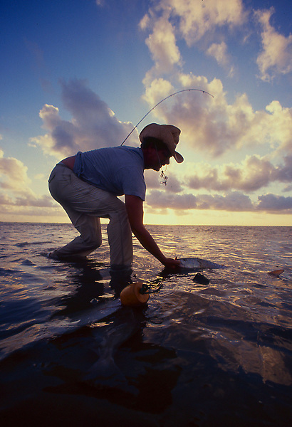 Stock photo of a man pulling a fish from the bay in Galveston Texas at sunset